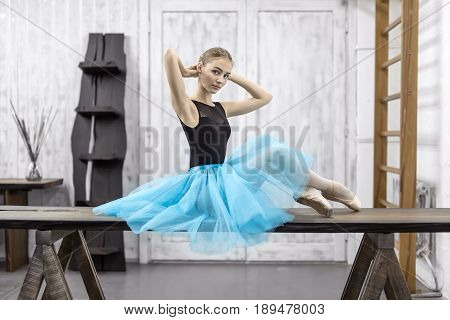 Attrective ballerina sits on the wooden table on the light wall background in the studio. She wears a black leotard with a cyan tutu and pointe shoes. She looks into the camera. Horizontal.