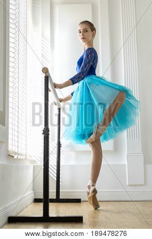 Amazing ballerina stands on the right toe next to the ballet barre on the white wall background. She wears a lace blue leotard, cyan tutu, pointe shoes and looks into the camera. Indoors.