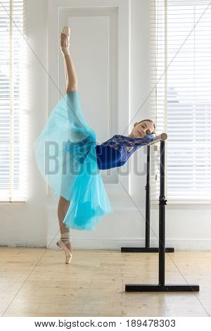 Tender ballerina with closed eyes does split while stands on the left toe and leans on a ballet barre on the white wall and windows background. She wears a lace blue leotard, cyan tutu, pointe shoes.