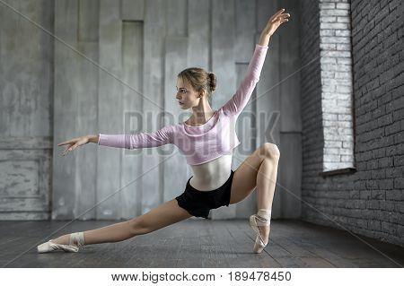 Beautiful ballerina posing next to the window on the gray wall background. Her arms and right leg stretched to the sides. Girl wears black shorts, light leotard with lilac blouse and pointe shoes.