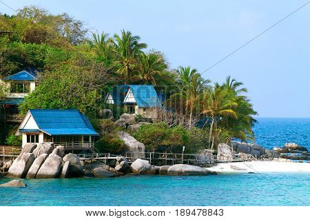 Green palm trees on the sea island among blue water. Tourist houses for rest.