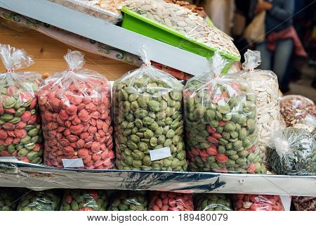 Many bags of various types of nuts for sale in a plastic bag.