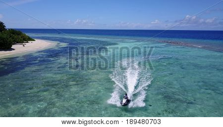 Aerial flying drone view of Maldives white sandy beach jetski riding sunny tropical paradise island with aqua blue sky sea water ocean 4k