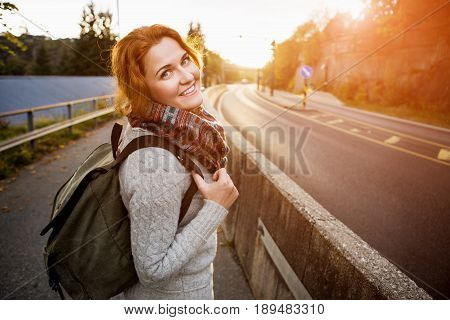 Hitch-hiking girl on a road in Europe