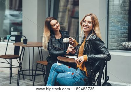 Group of european girls having a coffee together. Two women at cafe talking, laughing, gossiping and enjoying their time. Lifestyle, friendship and fashion concepts with real people models.