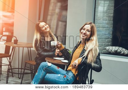 Two beautiful young women in fashion clothes having rest talking and drinking coffee in restaurant outdoor. concept of friendship lifestyle fashion. sunny day for walk with friends and have a fun.