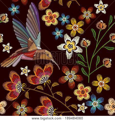 Humming bird and flowers embroidery seamless pattern. Beautiful hummingbirds and spring flowers embroidery on black background. Template for clothes textiles t-shirt design