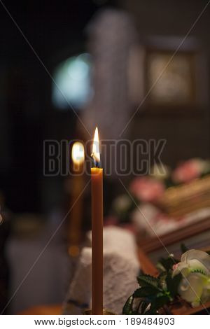 Typical votive candle in the darkness of a church light up for a prayer.
