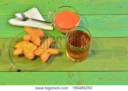 Hot tea and Youtiao (Cahkwe Cakwe Kueh Kuay Chinese Doughnut traditional Chinese Snack oil-fried pastry fried breadstick) put on old green wooden table. East and Southeast Asian cuisines