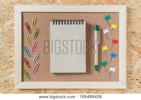 Blank notebook recycled paper with pen and paper clip and pin board on cork board and recycled wood. For your message or background image.