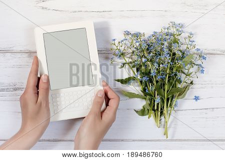 Woman hands holding white ebook, bouquet on a white rustic wooden background