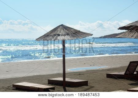 An Umbrella From The Sun Made Of Reeds And Wooden Sunbeds Stand Empty On The Beach, Sparkling Sea Wi