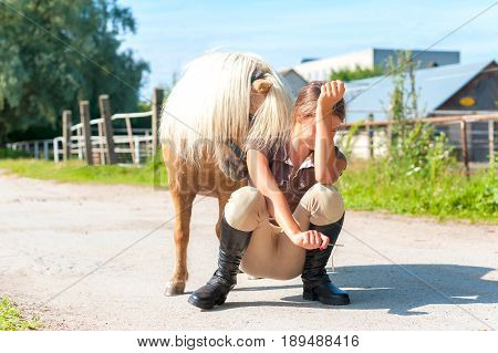 Lets play! Cheerful teenage girl sitting near cute little shetland pony. Summertime outdoors image.