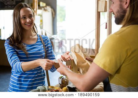 Smiling female customer paying bill by cash at bread counter in bakery shop