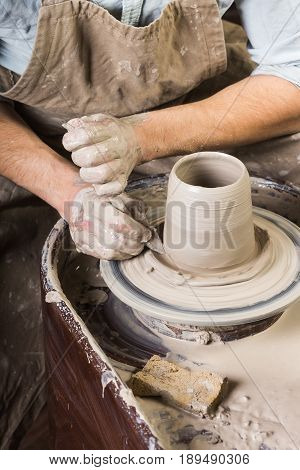 pottery, workshop, ceramics art concept - hands of a man works with potter's wheel, fingers form shape of raw fireclay, male master sculpts with a utensil with a sponge and carving tool, top view, vertical