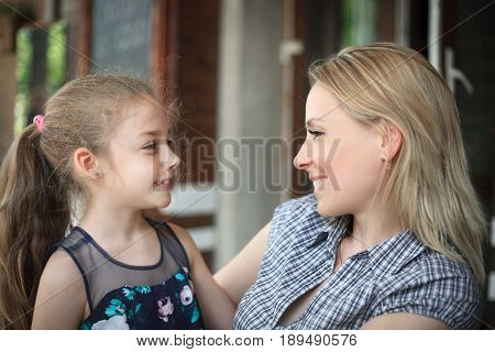 Portrait of a smiling young mother and daughter close-up outdoors. The concept of family relations.