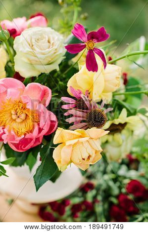 bouquet, holidays flower, floral arrangement concept - top view on flowers and buds in a pretty bouquet of pink peons, yellow and white roses, purple daisies and red carnations