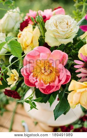 bouquet, holidays flower, gifts and floral arrangement concept - top view on vase of beautiful summer flowers, yellow and white roses, pink charming peon, carnations, selective focus