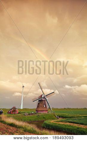 rainbow over Dutch windmill at sunset Holland