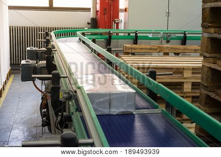 Package On Conveyor Belt Industrial Equipment Turn Curve Blue Moving Real