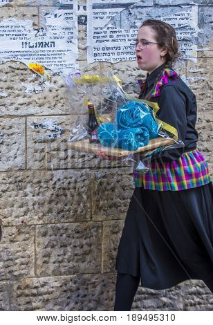 JERUSALEM - MARCH 13 : Ultra Orthodox woman holding Mishloach Manot during Purim in Mea Shearim Jerusalem on March 13 2017 Mishloach Manot is traditional food gifts given during Purim