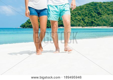 Couple walking on the beach in summer - lower bodies