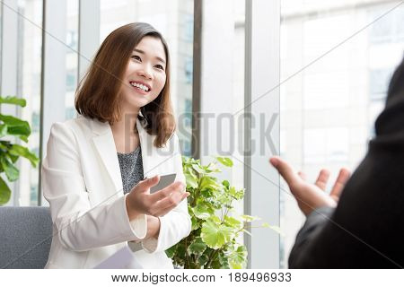 Smiling confident Asian business woman talking with client in ofiice lounge