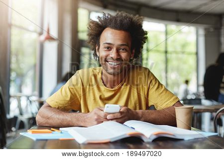 Funny Dark-skinned Man With African Hairstyle Working On Course Paper While Sitting In Cafe During L