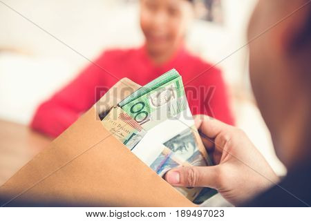 Businessman checking money Australian dollars in the envelope
