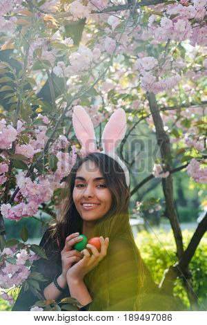 Woman With Bunny Ears Smiling With Colored Eggs, Sakura