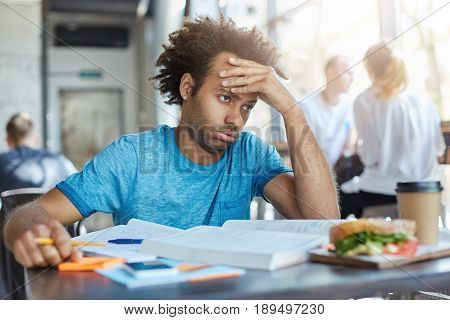 Candid Shot Of Frustrated Stressed Out Male Student Sitting At Cafe Table With Books, Notes And Lunc