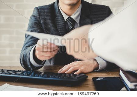 Businessman passing document to manager at the office