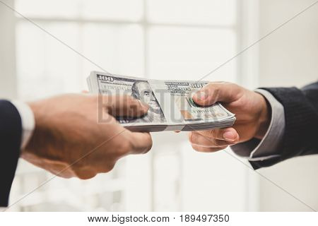 Businessman giving money US dollar bills to his partner - loanpayment bribery and corruption concepts