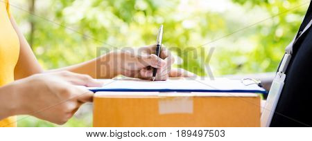 Woman signing document receiving package from delivery man - courier service concepts