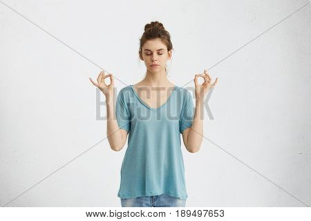 Yoga And Meditation. Beautiful Casually Dressed Young Woman Keeping Eyes Closed While Meditating, Fe