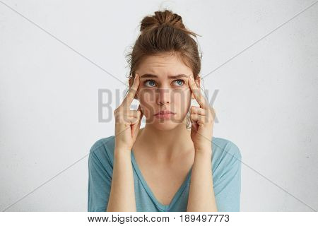 Portrait Of Tired Caucasian Blue-eyed Woman With Fair Hair Holding Fingers On Temples Looking Up Hav