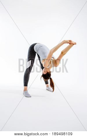 Young sportswoman exercises in yoga on an empty background