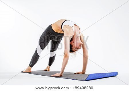 Sporty woman doing stretching exercise standing on hands and feet on rug at empty background