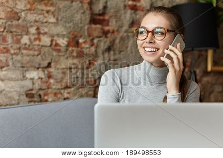 Positive Cheerful Young Caucasian Female Freelancer Talking On Mobile Phone While Sitting At Cafe Wi