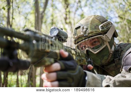 Soldier in helmet takes aim with gun in summer forest during day