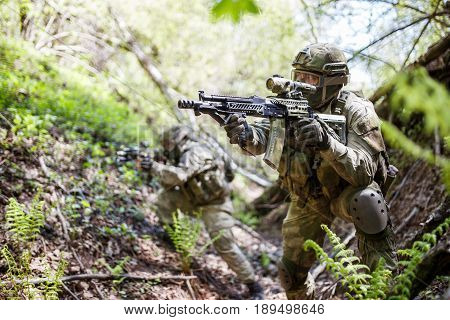 Military men with machine guns stand in ravine among trees