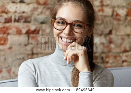 Happy Young Female With Charming Green Eyes Having Her Hair Tied In Pony Tail Wearing Big Glasses An
