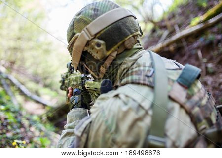 Photo from back of soldier in helmet on battlefield