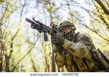 Soldier aiming holding submachine gun in forest on mission