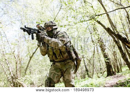 One officer with submachine gun in forest on reconnaissance