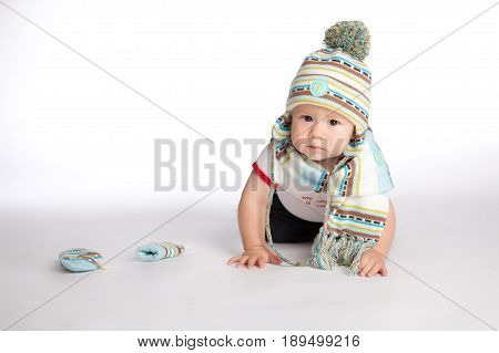 isolated baby boy in the striped hat and scarf of light tones took off his mittens and crawled on all fours forward