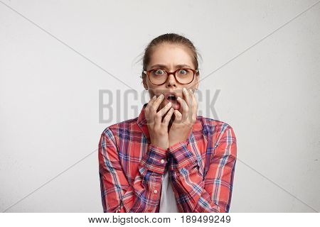 Terrified Wide-eyed Woman In Glass Spectacles And Red Checked Shirt Holding Her Hand On Opened Mouth