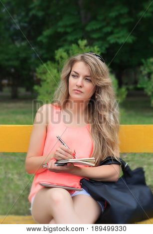 Beautiful young woman writes in a notebook sitting on the bench in the park.