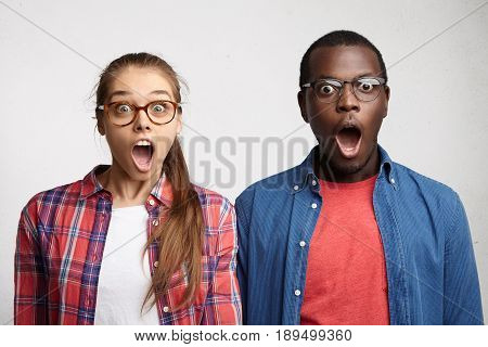 Surprised International Couple Looking With Great Surprise In Camera Isolated Over White Background.