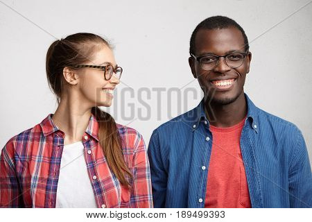 Young Mixed Race Couple: Woman With Pony Tail Wearing Eyeglasses And Checked Shirt Looking With Smil